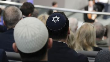 A file photo of two men wearing skullcaps as they listen to Israeli Historian Saul Friedlaender during a remembrance event of the parliament Bundestag to commemorate the victims of the Holocaust at the Reichstag building in Berlin.