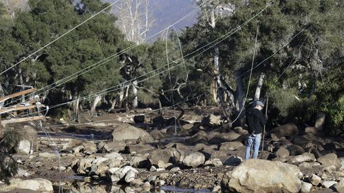 A man stands near downed power lines in Montecito, amid the destruction of a deadly mudslide. (AAP)