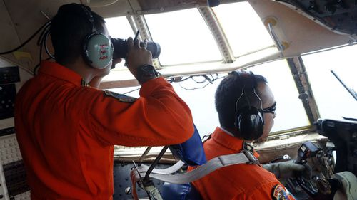 Indonesian Air Force members look out the cockpit windows of C-130 for the missing AirAsia jet. (AAP)