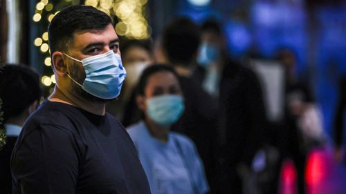 People in Sydney wear face masks as they stand in a line inside a shopping centre. Some LGAs in Sydney remain 'red-zoned' by Victoria.