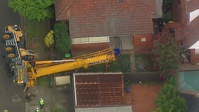 Driver trapped after crane collapses in Sydney's south-west