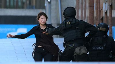 An armed tactical response police officer grabs a hostage as she runs to flee from a cafe under siege. (AAP)