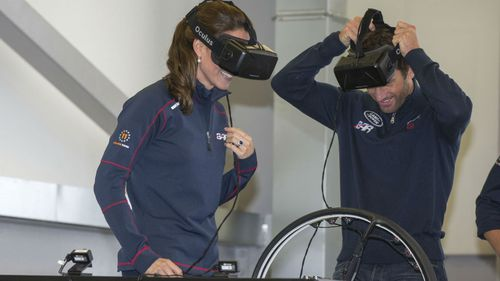 Kate, the Duchess of Cambridge, left, smiles as she joins sailor Ben Ainslie on a simulator.