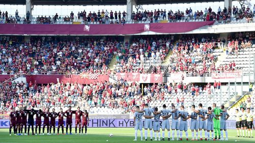 Players stand during the minute of silence in memory of the victims of the Genoa bridge collapse, prior to the Italian Serie A soccer match between Torino FC and AS Roma in Turin.