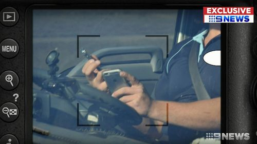 In one case, a male driver has a phone in each hand at the wheel and appears to be texting or actively using the touchscreen on one, while only the fingers of the other hand hang onto the wheel.
