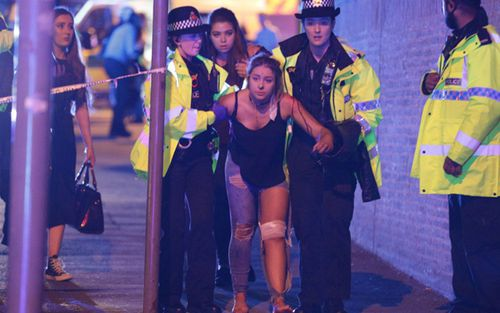 A victim of the suicide bombing at the Ariana Grande concert is led away by emergency workers in Manchester. Photo: Joel Goodman/LNP