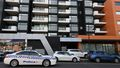 Police drive past the entrance of the Ariel Apartment complex in Melbourne, Australia.