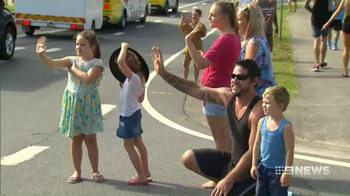 Crowds cheer the baton's arrival. (9NEWS)