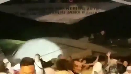 Patrons are seen running from the venue after the platform collapses.