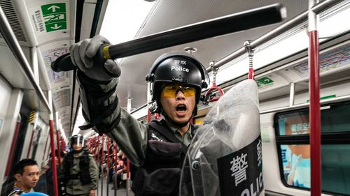 A Hong Kong police officer wields a heavy baton on a train.