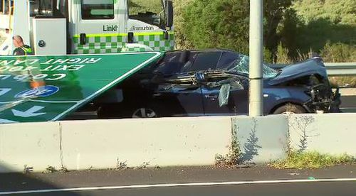 A woman has been taken to hospital after the overhead sign fell onto a car below.
