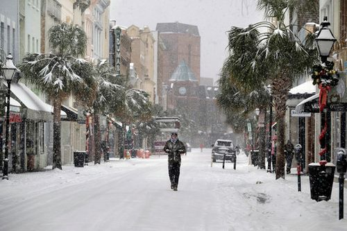 A person walks in the snow on King Street in Charleston, South Carolina.