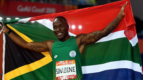 Akani Simbine holds the South African flag after winning the 100m. (AAP)