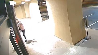 The woman is seen trying to open the door before returning with her vehicle.