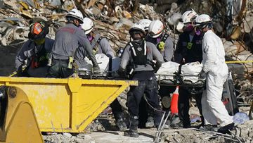 Search and rescue personnel remove remains on a stretcher as they work atop the rubble at the Champlain Towers South condo building where scores of people remain missing more than a week after it partially collapsed.