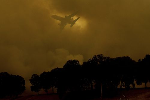An air tanker passes behind a smoke plume while battling the River Fire in Lakeport, Calif., on Monday, July 30, 2018. (AP Photo/Noah Berger, File)