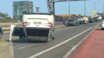 Car rolls onto roof after hitting tollgate on Harbour Bridge