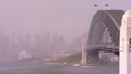 The dust obscures Sydney's CBD as it passes over the Harbour Bridge.