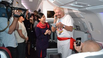 Virgin founder Richard Branson teaching Chinese on the airline's inaugural flight from Melbourne to Hong Kong.