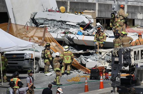Emergency crews are working to rescue people trapped beneath the collapsed bridge. (Getty)
