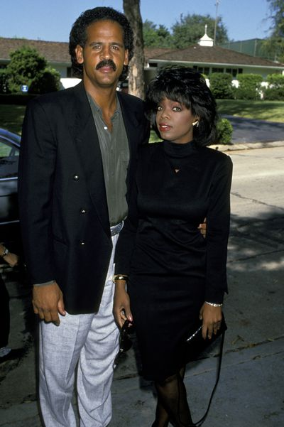 One of the early appearances of the talk show queen's signature bouffant hairstyle in 1989. Pictured with partner Steedman Graham