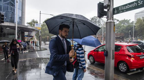 Workers tackle heavy rain in Sydney CBD, with more on the way.