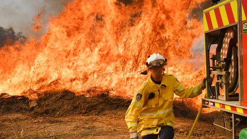 New South Wales Rural Fire Service firefighters are seen back burning and fighting fires on Long Gully Road in the northern New South Wales town of Drake, Monday, September 9, 2019. A number of homes have been destroyed by bushfires in northern New South Wales and Queensland. (AAP Image/Darren England) NO ARCHIVING