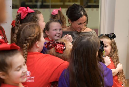 Ms Markle is swamped by her young adoring fans during a visit to Star Hub in Tremfora. (AAP)