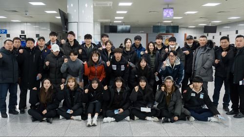 South Korean skiiers make a fist of solidarity before departing for the North for joint ski training with North Korean athletes. (AAP)