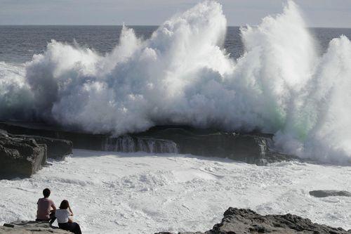 A couple watches waves hitting a coast of Shirahara town.