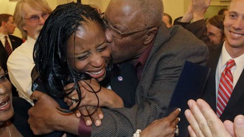 Mia Love is embraced by her Haiti-born father during her election night party in 2014. (AAP)