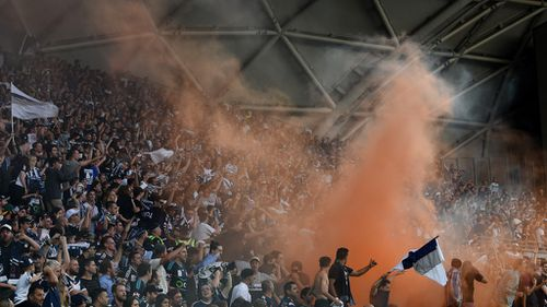 Melbourne Victory fans light a flare during the Melbourne City and Melbourne Victory A League round 19 match at AAMI Park. (AAP)