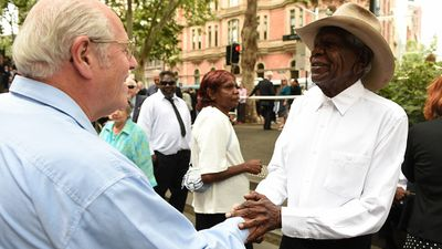 Jimmy Wavehill, (right), from Wavehill Station in the Northern Territory is greeted by a friend as they gather for the memorial service. (AAP)