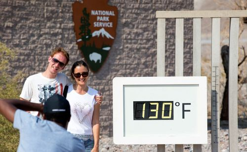 A couple poses at the Furnace Creek Visitor Center thermometer in Death Valley National Park, California.
