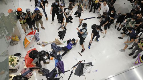 Policemen scuffle with protesters inside a shopping mall in Sha Tin District in Hong Kong.