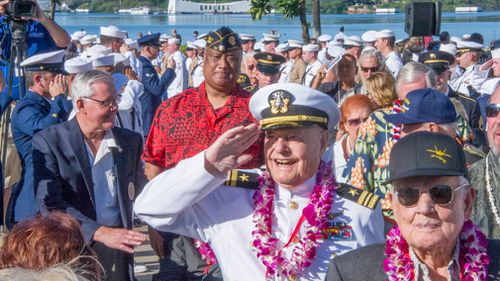 Arizona survivor, Louis Conter, centre, salutes as he leaves the National Pearl Harbor Remembrance Day ceremony. (AAP)