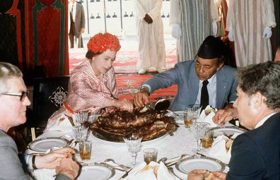 Queen Elizabeth II eats with her hands in the desert with King Hassan during her visit to Morocco on October 27, 1980.