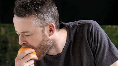 Hamish Blake biting into an orange with the skin on, because why not?