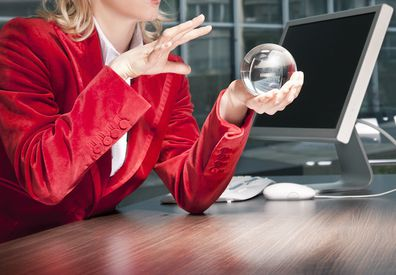 Woman looking into crystal ball in office