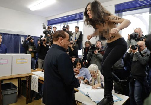 "The Italian election protester had ""Berlusconi, you expired"" scrawled on her body, at the Milan polling station on Sunday, March 4. (AAP)"