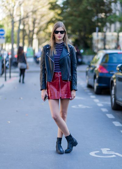A model wearing a red latex skirt and leather jacket outside Ellery, Paris Fashion Week
