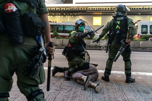 Riot police arrest a man during an anti-government protest.