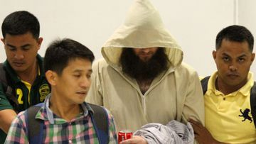 Philippine police operatives escort Australian Islamic preacher Robert Cerantonio, alias Musa, upon their arrival at the Ninoy Aquiono International Airport in Manila, Philippines, Friday, July 11, 2014