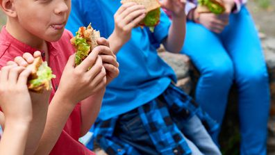 Kids eating good food sandwiches