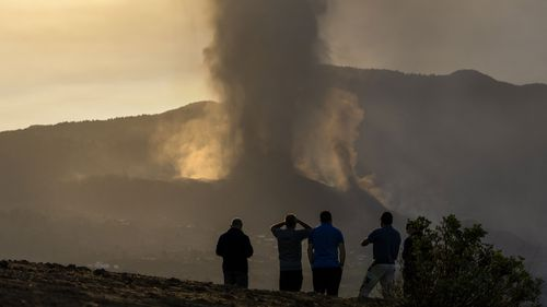 Residents watch from a hill as lava continues to flow from an erupted volcano, on the island of La Palma in the Canaries, Spain.