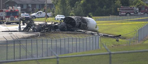 The burned remains of a plane that was carrying NASCAR television analyst and former driver Dale Earnhardt Jr. lie near a runway in Elizabethton, Tennessee.