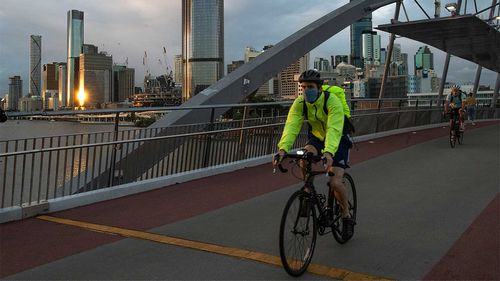A masked cyclist travels along Southbank in Brisbane.