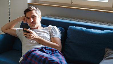 Man sitting on his lounge using his phone.