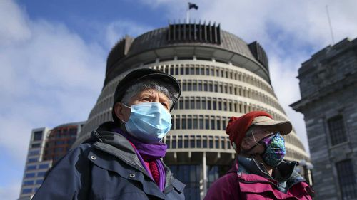 Two women pose in front of the Beehive while wearing face masks ahead of a COVID-19 Alert Level announcement on August 14, 2020 in Wellington, New Zealand.