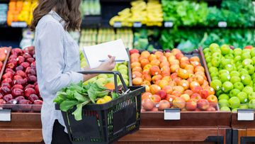 Woman grocery shopping stock generic